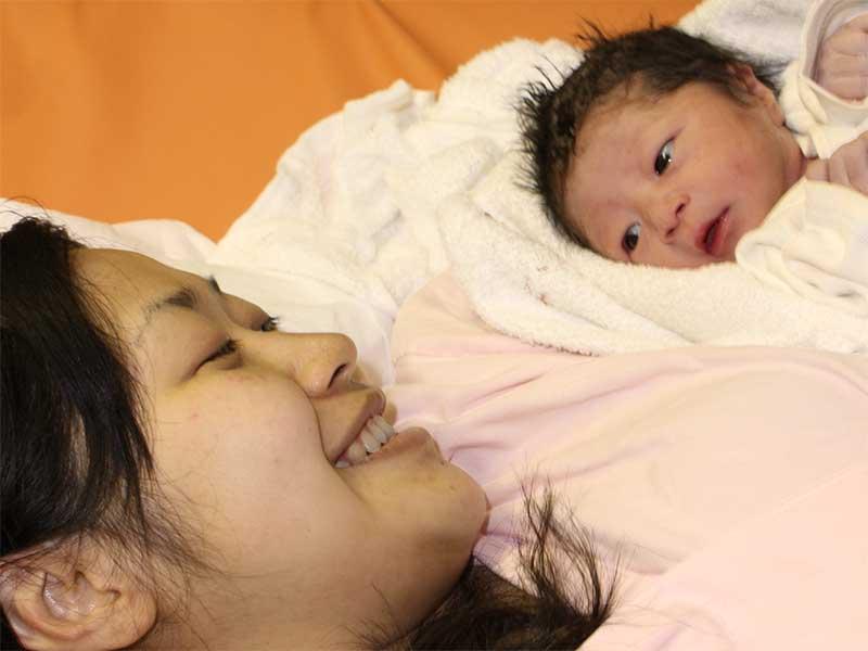 生まれた赤ちゃんを見つめる母親