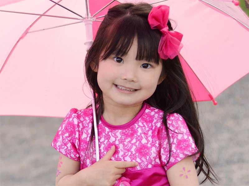 笑顔で傘を差してる女の子