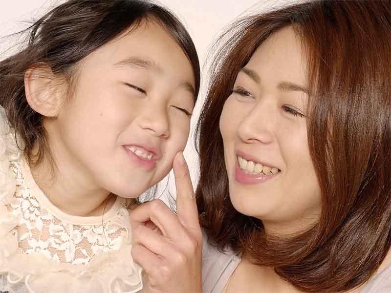 女の子の顔を触ってスキンシップをとってるママ
