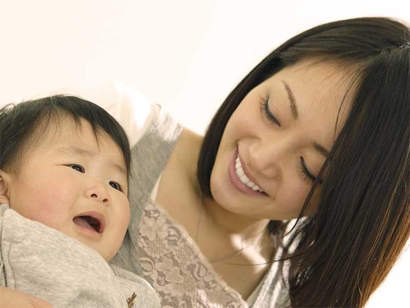 泣いている赤ちゃんとなだめてるママ