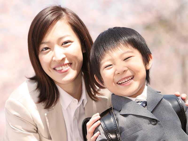 ランドセルを背負った小学生の男の子と母親