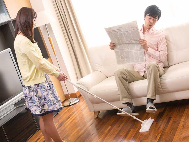 掃除をしている妻と掃除の邪魔になってる新聞を読んでる旦那