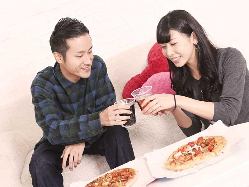 家事分担のご褒美にピザとビールで乾杯している夫婦