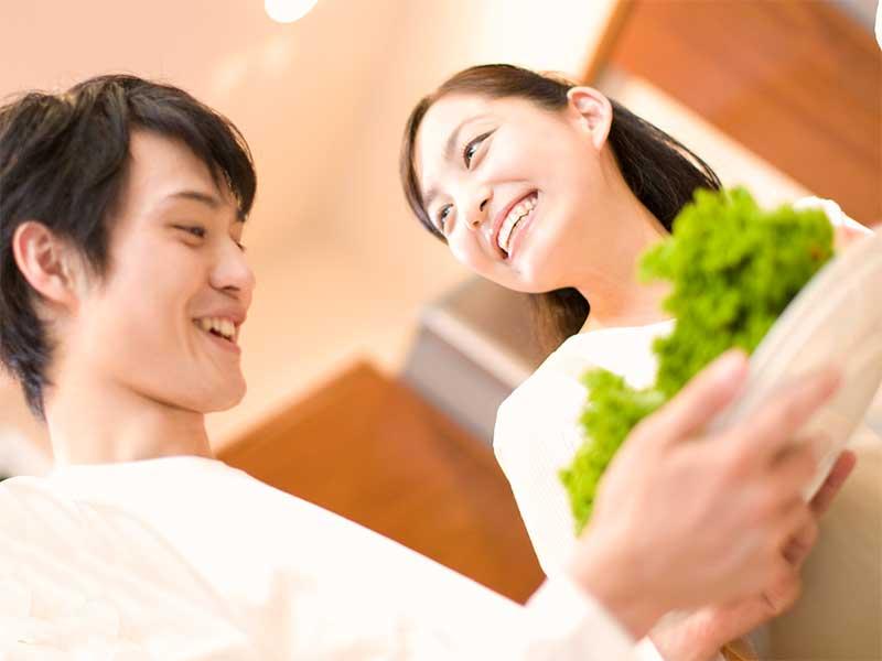 一緒にサラダを作っている笑顔の夫婦