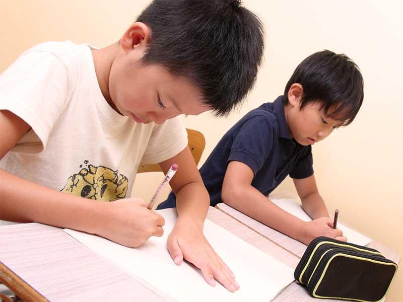 机に座って筆記テストをしてる小学生