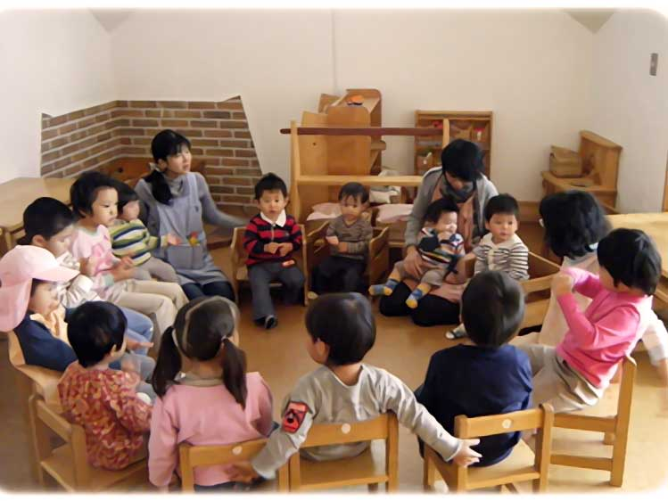 輪になって話をしてる幼稚園児達