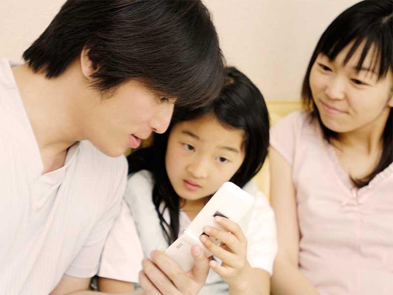 携帯の使い方を教えているパパ