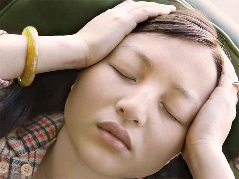 頭痛で頭を抱えてる女性