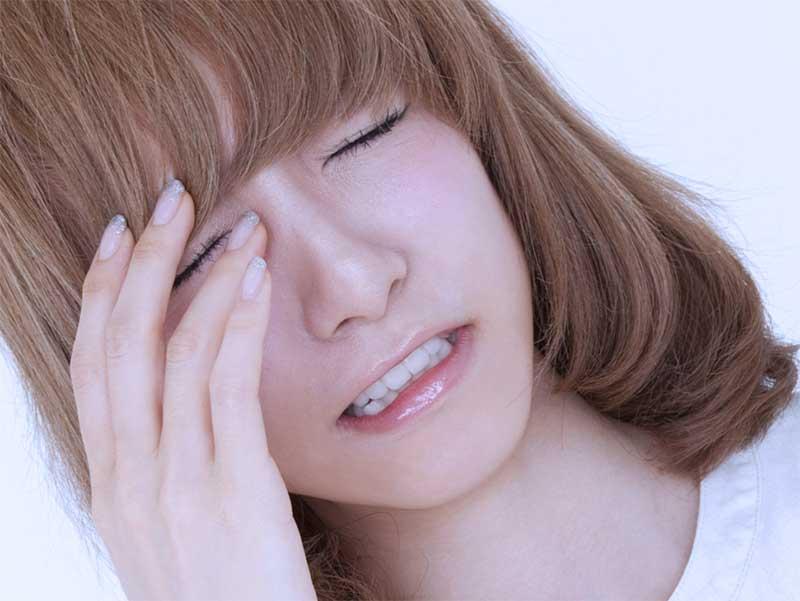 偏頭痛でこめかみを手で抑える嫁