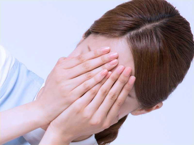 憂鬱で顔を手で覆っている奥さん