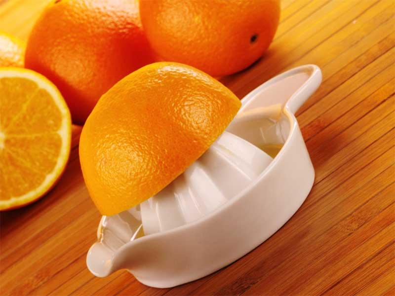 絞り器でオレンジ果汁を作ってる
