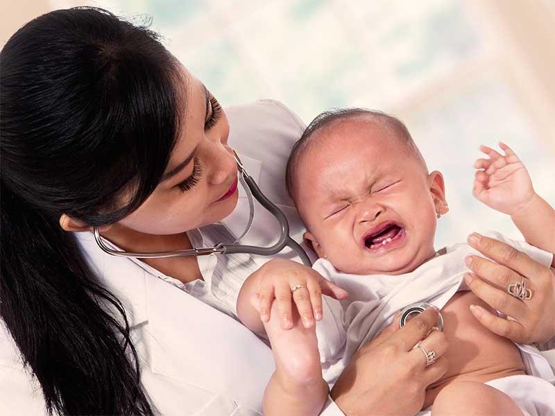 病院で医者に鼻づまりを見てもらってる赤ちゃん