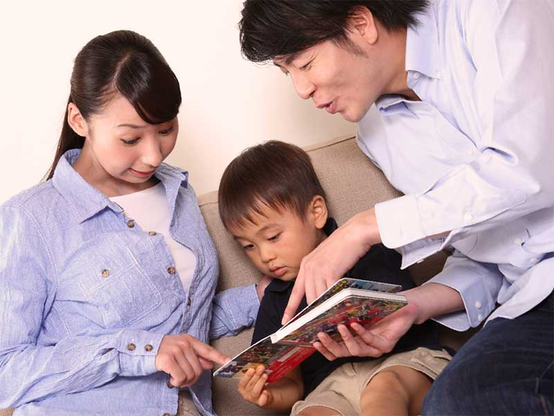 パパとママの間に座って絵本を読んでもらってる子供