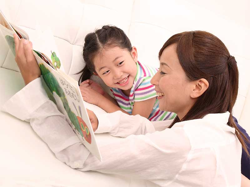 ママと一緒に絵本を見てる子供