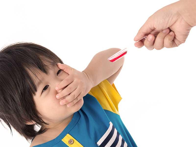口を手で塞いで薬を飲むのを拒否している赤ちゃん
