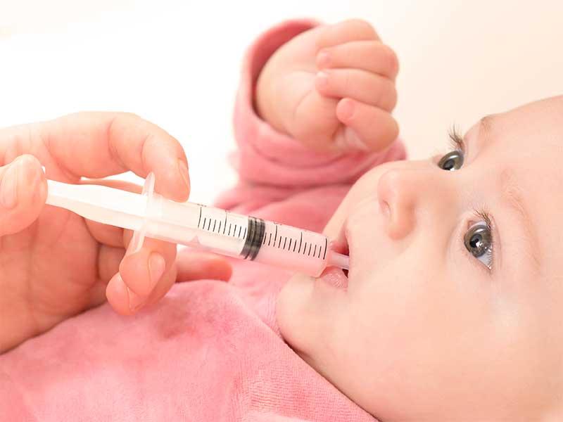 スポイトを使って赤ちゃんに薬を飲ませてる母親