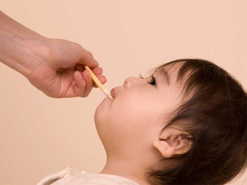 母親からスプーンで薬を飲まされてる赤ちゃん