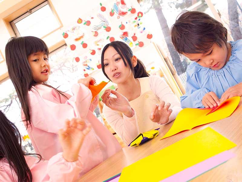 園児が折り紙してるのを見守る幼稚園教師