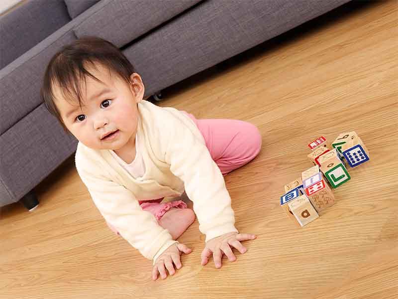 玩具の前に座ってる赤ちゃん