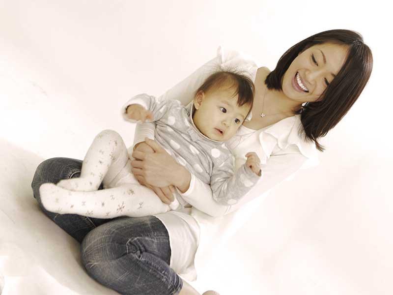 赤ちゃんを膝の上に乗せて抱っこしてる正座してるママ