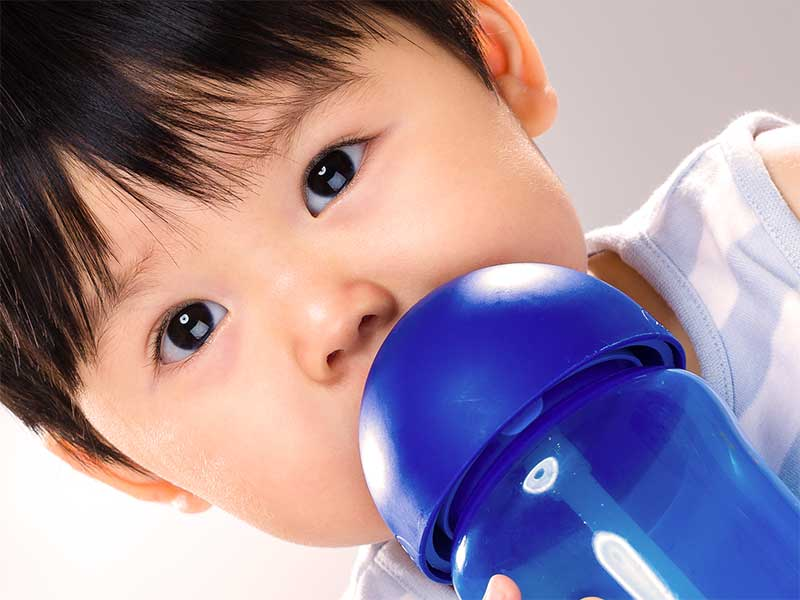 ストローマグでジュースを飲んでる赤ちゃん