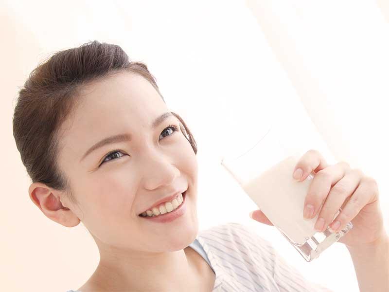 笑顔で牛乳を飲んでる女性