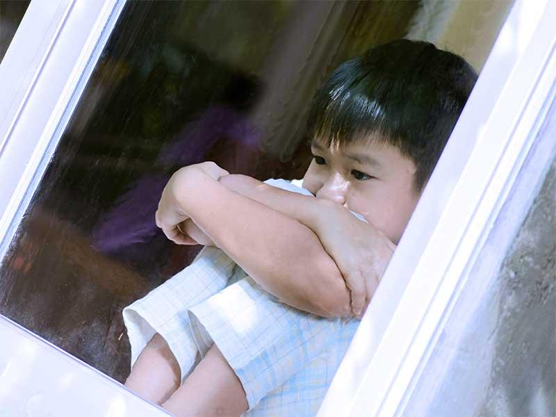 窓際で体育座りして悩んでる子供