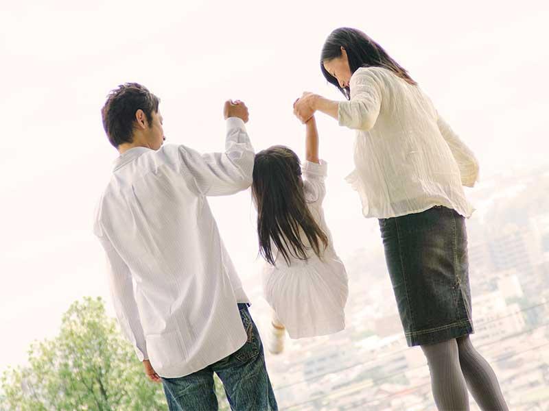 両親と手を繋いで歩いている女の子