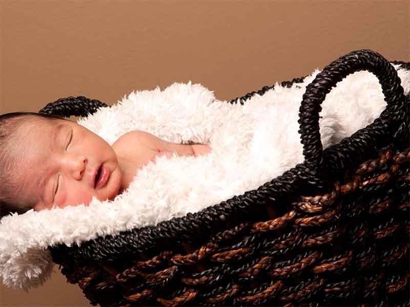 籐製のクーファンで寝てる赤ちゃん