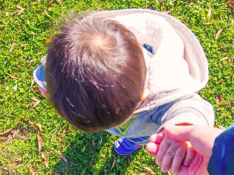 ママに手を惹かれたフード付きのパーカーを着てる子供