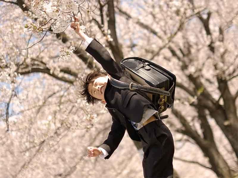 ランドセルを背負ったまま公園で遊んでる男の子