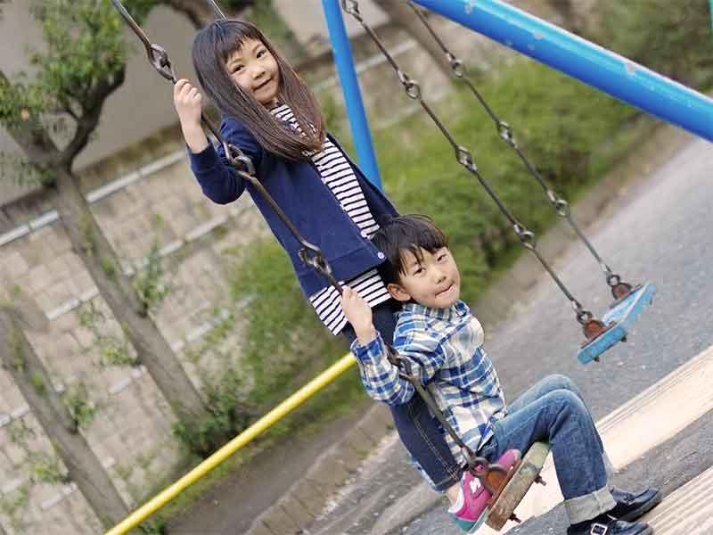 1つのブランコで遊んでる男の子と女の子