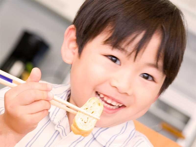 箸を使って玉子焼きを食べようとしてる男の子