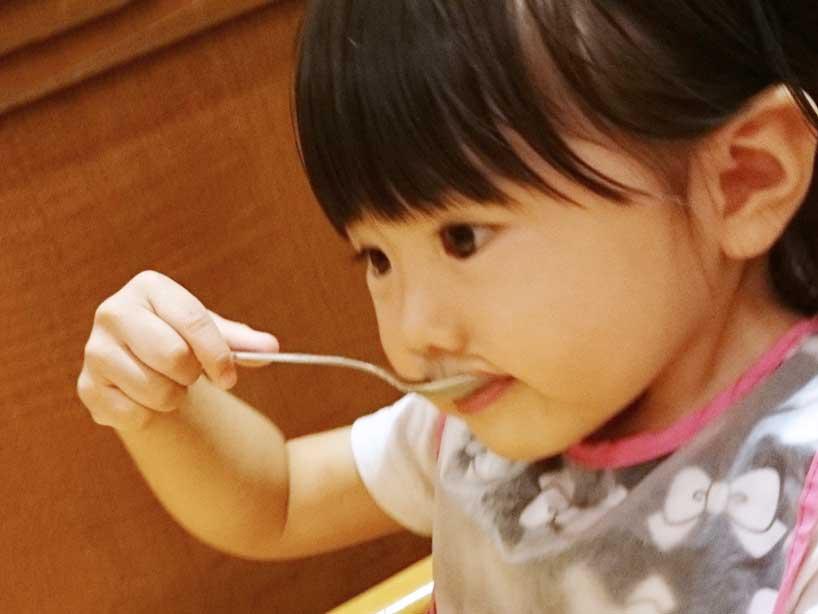 スプーンでスープを飲んでる女の子