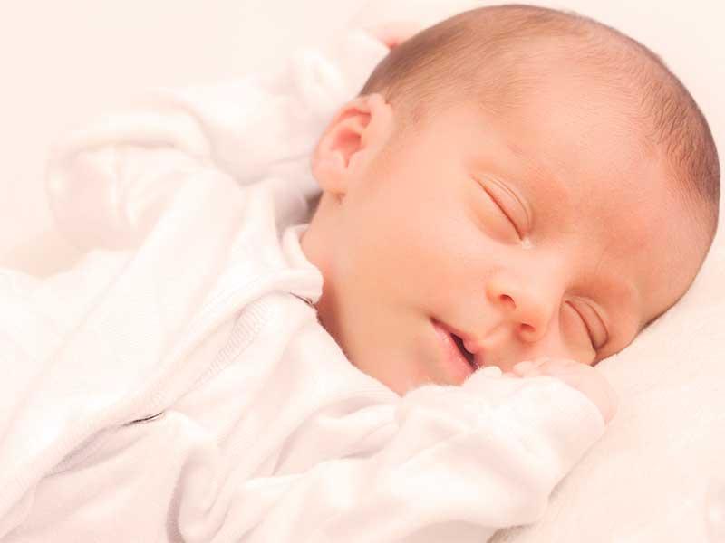 長袖の肌着を着て静かに寝てる赤ちゃん