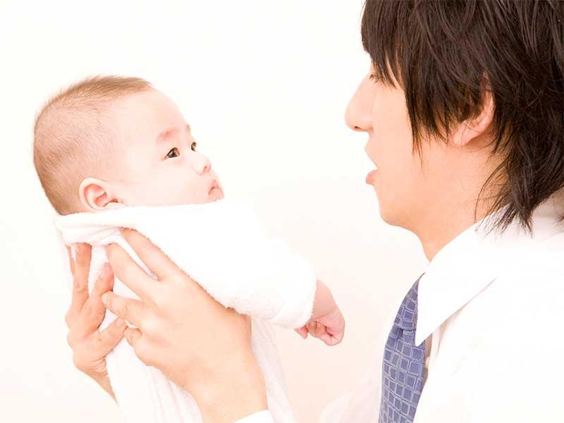 赤ちゃんを抱き上げてスキンシップしてるパパ