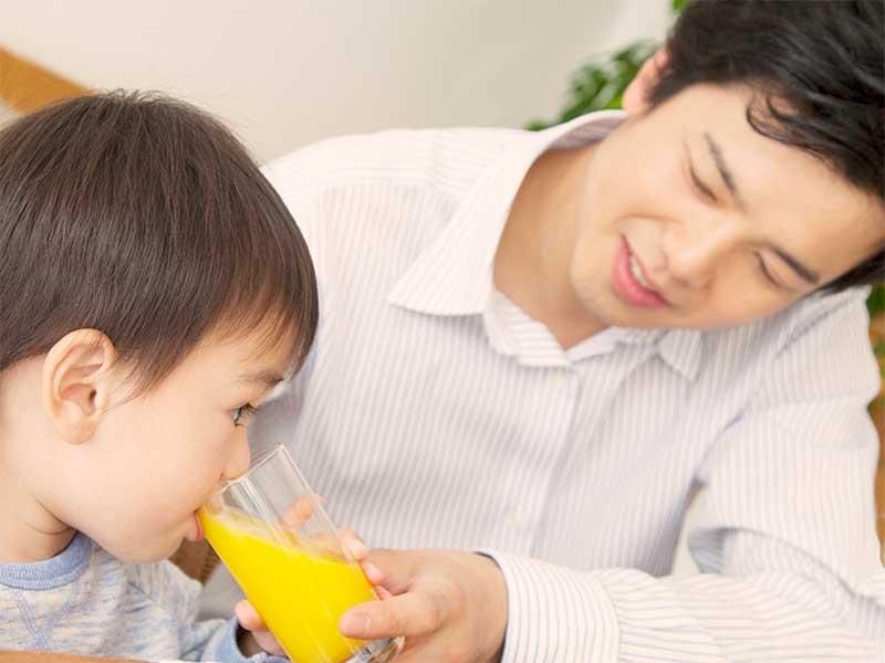 男の子にオレンジジュースを飲ませてあげてるパパ