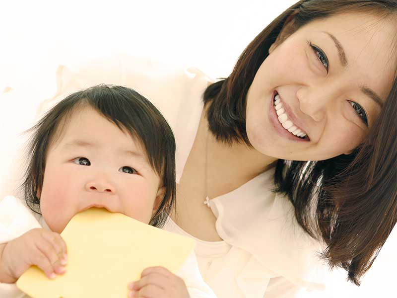 ママに抱っこされながら玩具を噛んでる赤ちゃん