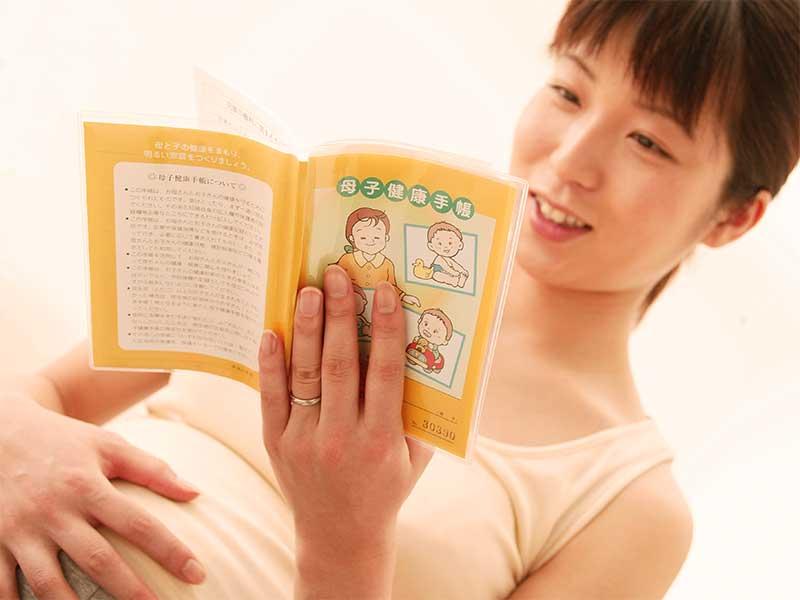 母子手帳を読んで安静にしてる妊婦さん