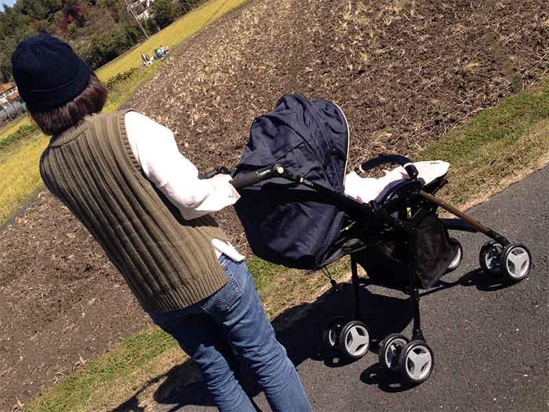 ベビーカーに赤ちゃんを乗せて散歩してるママ