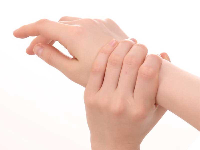腱鞘炎の痛みで手首を押さえてる女性