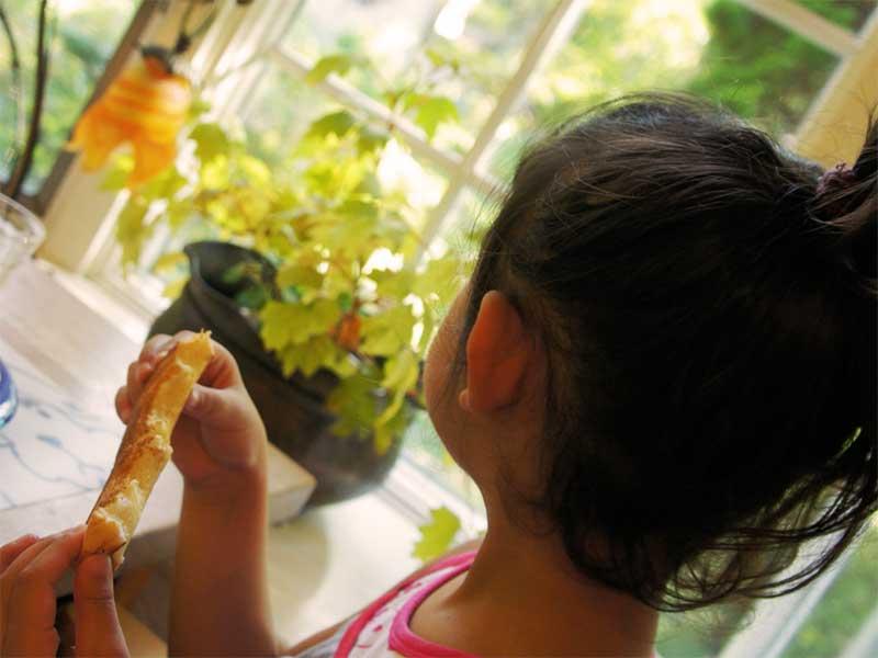 よそ見をしながらご飯を食べてる子供