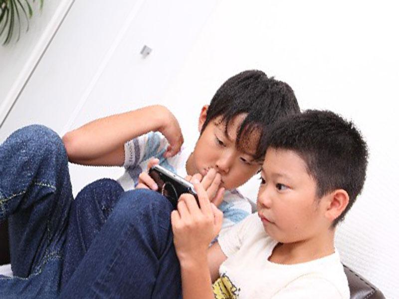 男の子二人がゲーム機であそんでいる