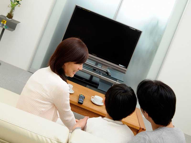 明るい部屋でテレビを見ている家族