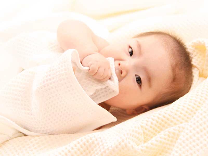 布団に包まって寝返りをうってる赤ちゃん