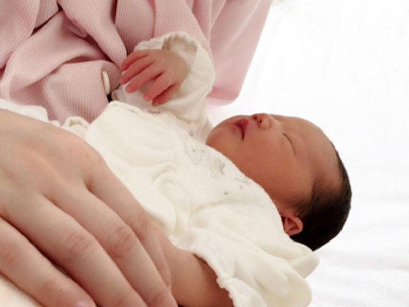 生まれたばかりの赤ちゃんを抱っこしてる