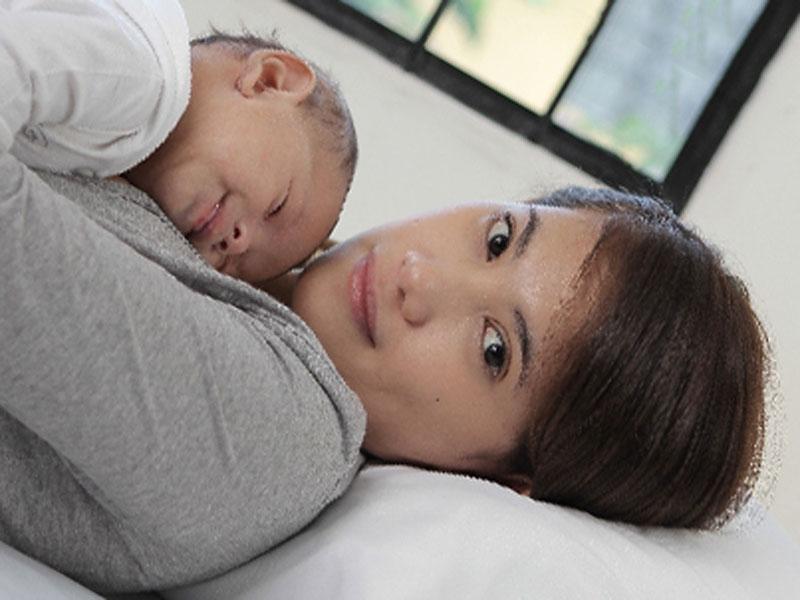 横になっているお母さんの上で寝ている赤ちゃん