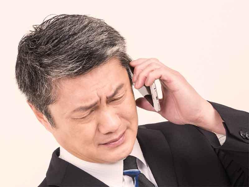 仕事の電話でストレスを感じてる男性