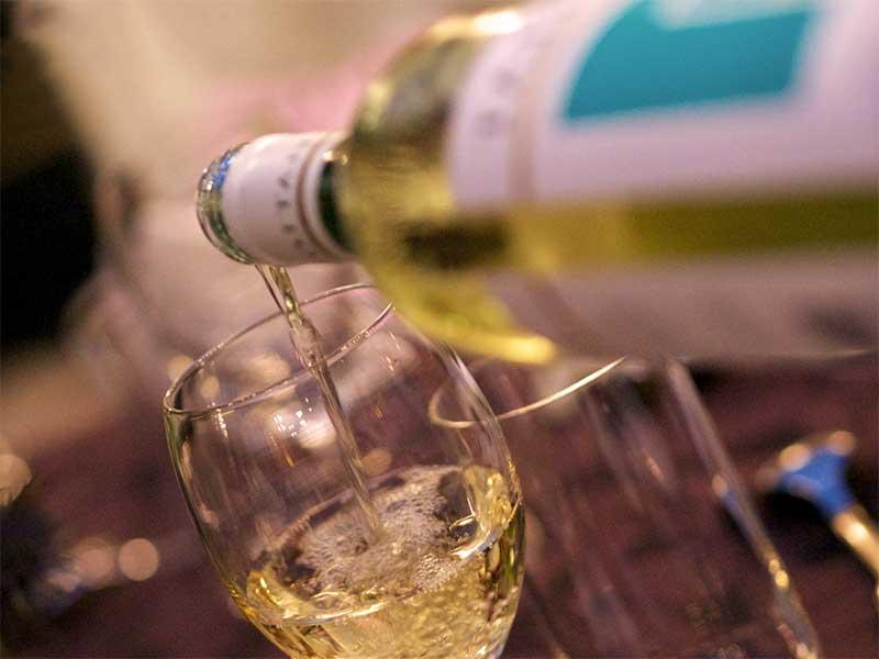 グラスにワインを注いでる