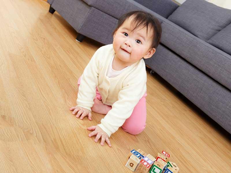 家の床で遊んでいる赤ちゃん